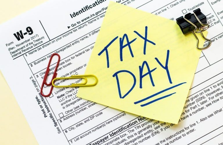 A W9 tax form with tax day written on a sticky note.